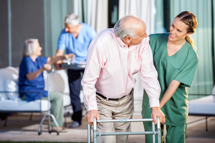 Happy female caretaker assisting senior man in using Zimmer frame at nursing home yard