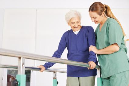Physiotherapeutin hilft einer alten Seniorin auf einem Laufband bei der Physiotherapie